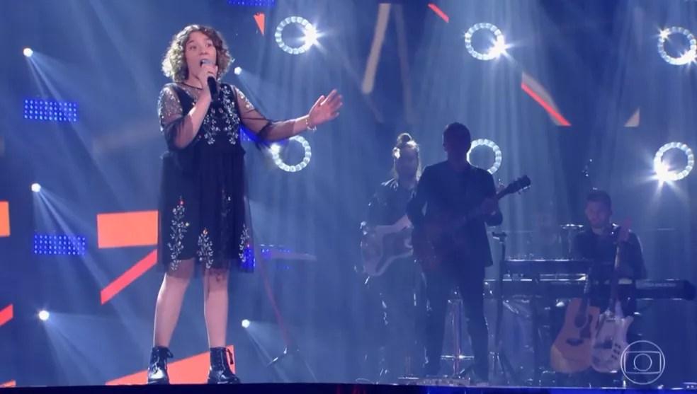 Camila Woloszyn emociona em sua apresentação no 'The Voice Kids' — Foto: TV GLOBO