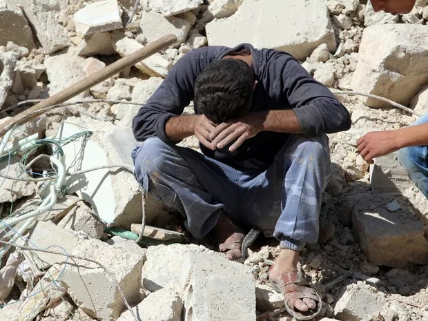 Homem fica desolado em meio a destroços após ataque aéreo em Aleppo (Foto: Abdalrhman Ismail/Reuters)