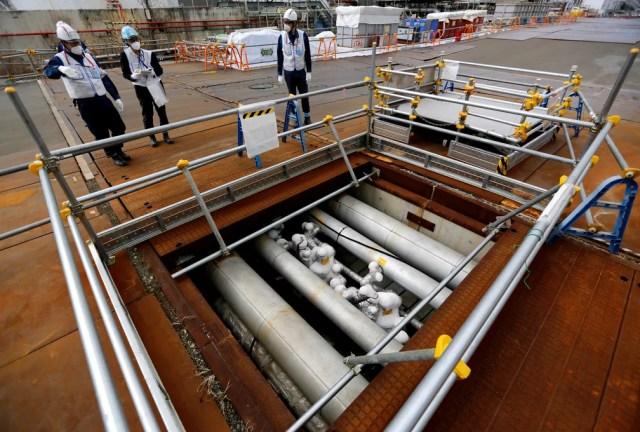 Trabalhadores da Tepco observam barreira para impedir vazamento de água contaminada na usina de Fukushima, no Japão — Foto: Issei Kato/Reuters