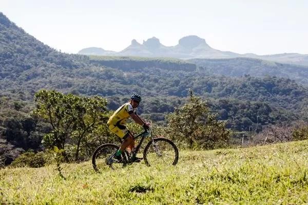 Ciclista pedala com o belo visual da Cuesta ao fundo