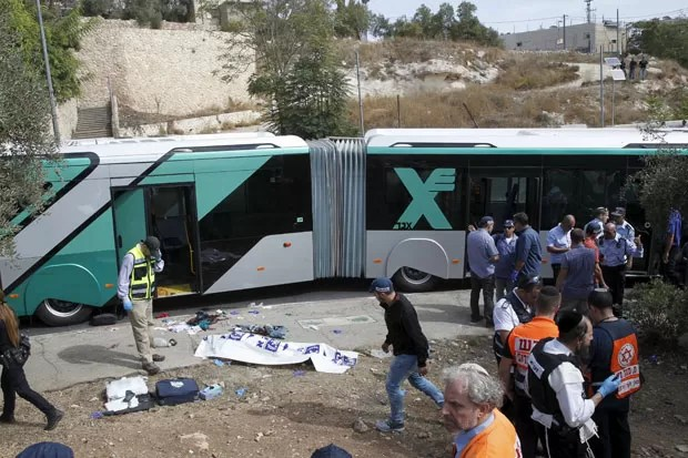 Equipes de emergência são vistas em local de ataque em Jerusalém nesta terça-feira (13); duas pessoas abriram fogo em um ônibus (Foto: Ronen Zvulun/Reuters)