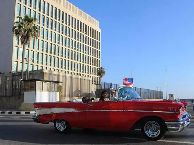 Carro com bandeira dos Estados Unidos passa em frente ao prédio da embaixada do país em Havana nesta segunda-feira (20) (Foto: AFP PHOTO/YAMIL LAGE)