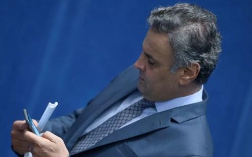 Na noite de ontem Aécio Neves foi visto lendo o noticiário no celular e, em seguida, deixou o Congresso. (Foto: Jorge William / Agência O Globo)