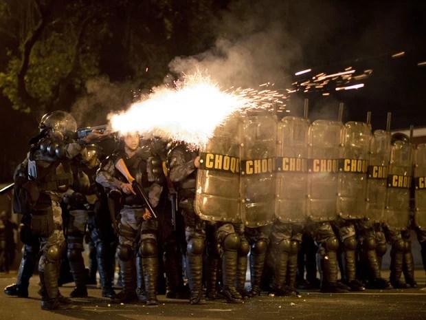 Policiais disparam bombas de gás lacrimogêneo contra manifestantes no Palácio Guanabara, no Rio, nesta segunda-feira (12). (Foto: Felipe Dana/AP)