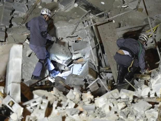 Homens do Corpo de Bombeiros buscam por vítimas em meio aos escombros de prédio em obras que desabou em Guarulhos, SP. (Foto: José Patrício/ Estadão Conteúdo)