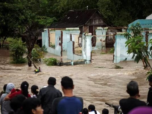 Pessoas obaservam área inundada na área residencial Kampung Sewu, em Solo, na província de Java Central, na Indonésia, neste domingo (19)  (Foto: Antara Foto/Maulana Surya/via Reuters)