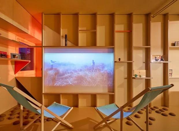 Na sala, há espaço para receber amigos. Com poucos móveis grandes, o local usa um telão como TV (Foto: José Hevia./ Dezeen)