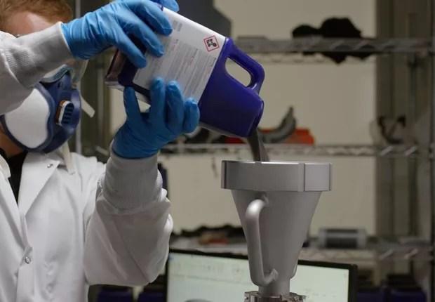 Um técnico despeja pó de metal em uma tremonha de uma impressora 3D de sinterização a laser usada pelo Relativity Space. (Foto: Divulgação)