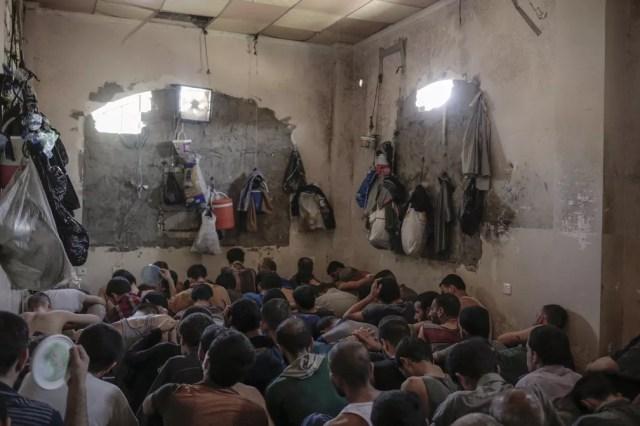 Suspeitos de serem membros dos Estado Islâmico são fotografados em pequena prisão em Mossul (Foto: AP Photo/Bram Janssen)