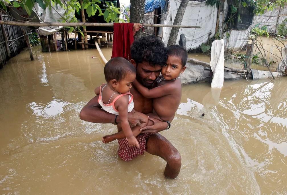 5 de junho - Um homem carrega seus filhos para fora de sua cabana durante uma inundação após fortes chuvas nos arredores de Agartala, na Índia, no Dia Mundial do Meio Ambiente (Foto: Jayanta Dey/Reuters)