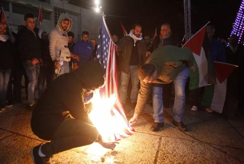 Manifestantes queimam bandeira dos EUA em protesto em Belém após anúncio de Trump de reconhecer Jerusalém como a capital de Israel (Foto: Musa Al Shaer / AFP Photo)