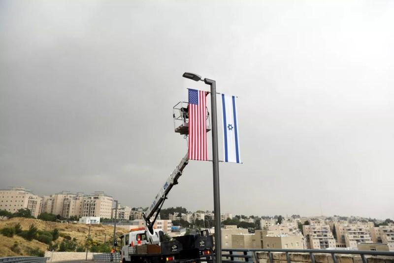 Funcionário instala bandeira americana ao lado da bandeira de Israel em local perto da entrada do consulado americano em Jerusalém, onde também funcionará a embaixada dos EUA — Foto: Ronen Zvulun/ Reuters