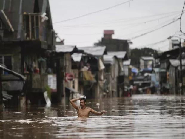 Morador atravessa rua alagada com água à altura do peito em Marinika, na região metropolitana de Manila, Filipinas. As chuvas de monção, somadas a uma tempestade tropical, inundaram metade da capital filipina, causando ao menos 7 mortes. (Foto: John Javellana/Reuters)