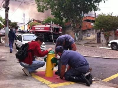 Bombeiros trabalham para abrir hidrante em rua vizinha ao incêndio (Foto: Paulo Toledo Piza/G1)