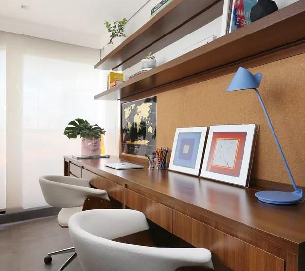 A varanda do quarto do casal foi integrada ao ambiente para receber o escritório, com desenho do estúdio Loft87 e execução da marcenaria Lumax. Objetos da Dpot e quadros da Galeria Papel Assinado (Foto: Mariana Orsi/Divulgação)