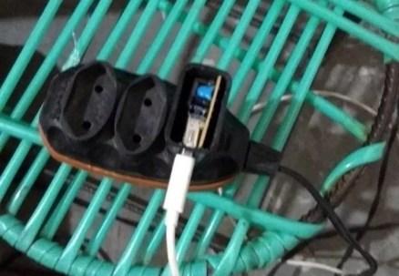 Mulher morreu após receber descarga elétrica de carregador de celular enquanto usava o aparelho (Foto: Polícia Militar/Divulgação)