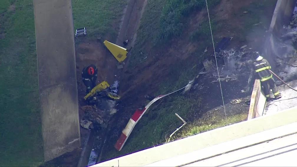Bombeiros recolhem peças do helicóptero que caiu na Anhanguera — Foto: TV Globo/Reprodução