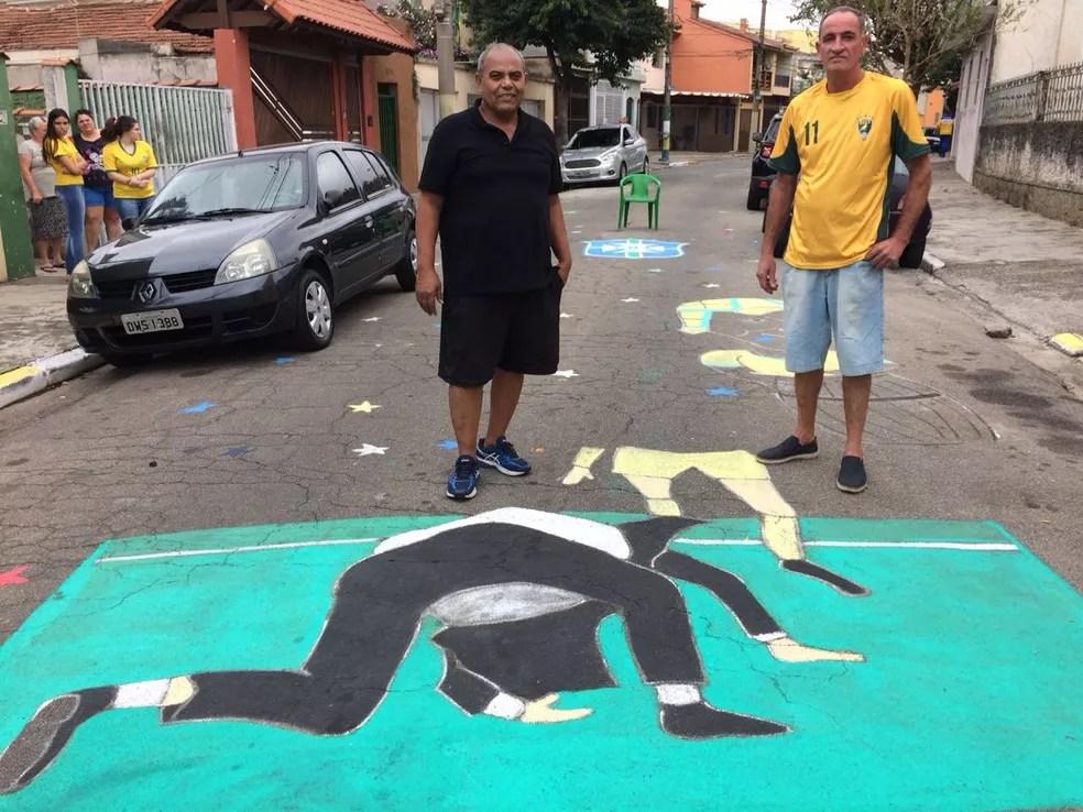 Roberto e Remo posam com o desenho do tombo de Tite no asfalto (Foto: Bárbara Muniz Vieira/G1)