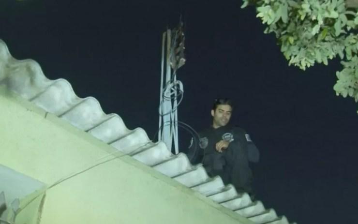 Policial vistoria rede de energia de casa em Birigui (Foto: Reprodução/TV TEM)