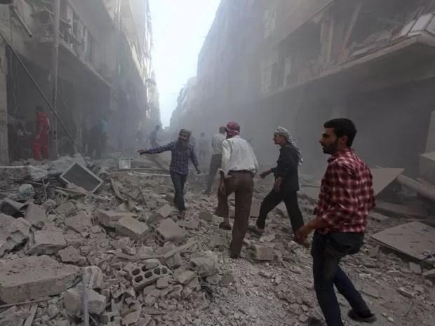 Moradores circulam em área atingida por bombardeios nesta sexta-feira em Douma (Foto: Badra Mamet/Reuters)