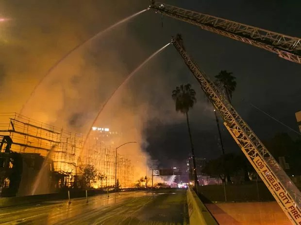 Bombeiros de Los Angeles trabalham em incêndio nesta segunda-feira (8) em de Los Angeles (Foto: AP Photo/Damian Dovarganes)