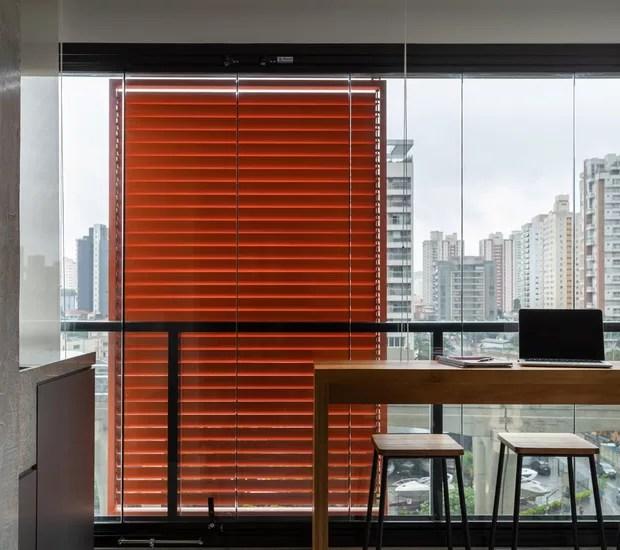 A varanda também funciona como home office ou bancada de refeições com vista da Av. Roberto Marinho à noite (Foto: Lufe Gomes/Divulgação)
