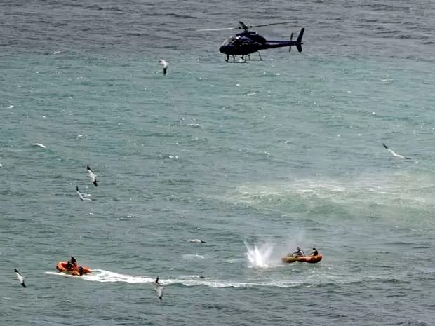 Policiais patrulham e até disparam contra um tubarão nas águas da praia de Muriwai Beach. (Foto: Ross Land / AP Photo)