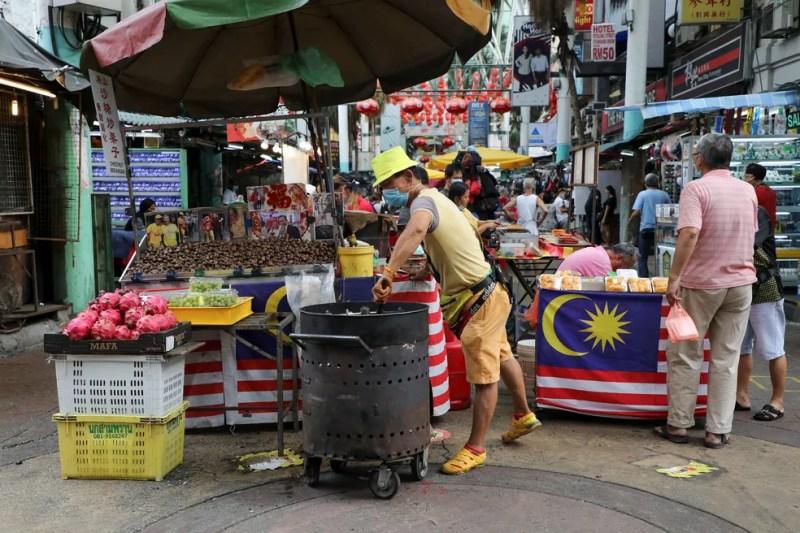 Vendedor com máscara espera os clientes em sua barraca em Chinatown, em Kuala Lumpur, na Malásia, nesta terça-feira (18) — Foto:  Lim Huey Teng/ Reuters