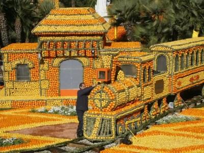 Trabalhador faz últimos ajustes em trem feito com limões e laranjas, durante o 80° Festival do Limão em Menton, no sul da França. Neste ano, o tema do festival, que envolve mais de 145 toneladas de frutas cítricas, é 'Volta ao Mundo em 80 dias' (Foto: Lionel Cironneau/AP)