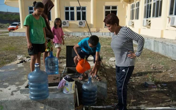 Indonésios buscam água — Foto: Bay Ismoyo / AFP
