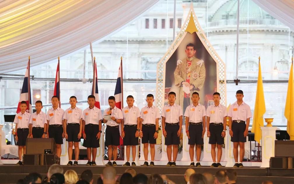 Integrantes do time 'Javalis Selvagens' fazem agradecimento em frente ao retrato do rei da Tailândia, Maha Vajiralongkorn Bodindradebayavarangkun, durante evento intitulado 'Unidos como um', em Bangcoc, na quinta-feira (6) (Foto: AP Photo/Sakchai Lalit)