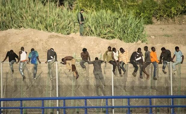 Imigrantes africanos escalam cerca ao tentarem entrar no enclave espanhol de Melilla nesta terça-feira (12) (Foto: Jesus Blasco de Avellaneda/Reuters)