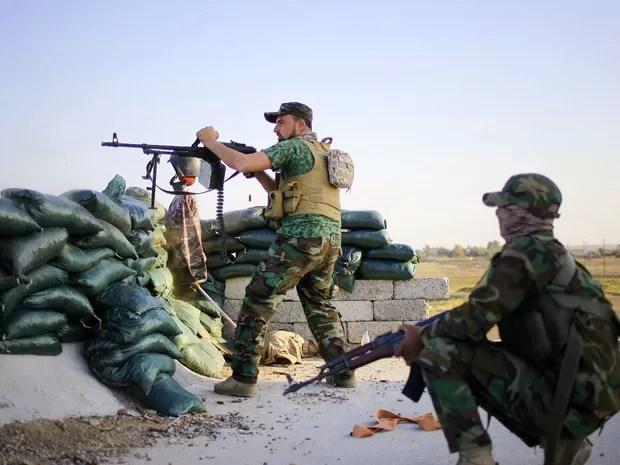 No sábado (21), voluntário junto a um grupo xiita aponta sua arma durante confronto com o Estado Islâmico nas imediações de Tikrit, ao norte de Bagdá, no Iraque (Foto: AP Photo)