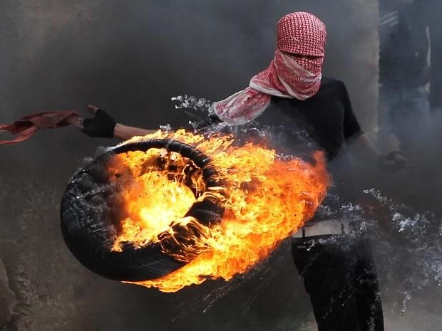 Palestino atira um pneu em chamas contra soldados israelenses durante conflito em Betunia, perto de Ramallah, Cisjordânia. Centenas de manifestantes entraram em choque com militares israelenses após uma marcha marcando os 65 anos do 'Dia da Catástrofe'. (Foto: Abbas Momani/AFP)