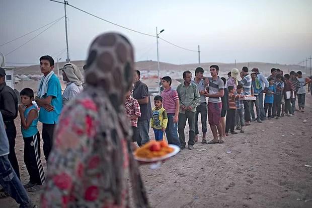 Refugiados fazem fila para comer no campo de Kawergost (Foto: Lynsey Addario/The New York Times)