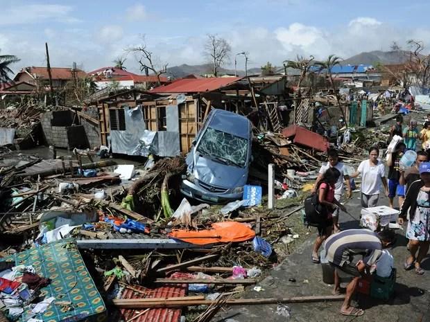 Moradores andam por região devastada por supertufão na cidade de Tacloban (Foto: Ted Aljibe/ AFP)