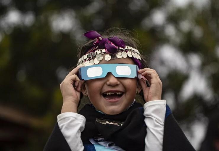 Menina indígena Mapuche sorri ao olhar para um eclipse solar total usando óculos especiais em Carahue, região chilena de Araucania, nesta segunda-feira (14). — Foto: Esteban Felix/AP