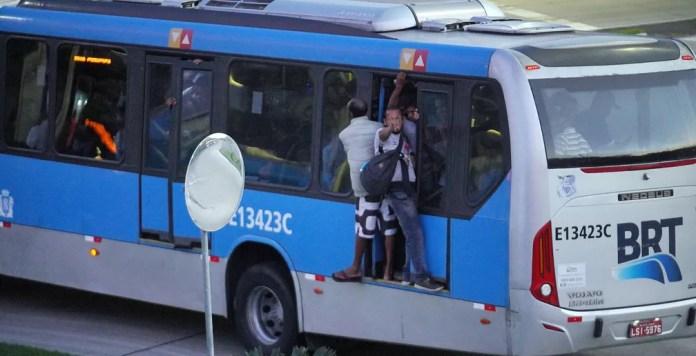 Passageiros andam do lado de fora do BRT lotado — Foto: Marcos Serra Lima/G1