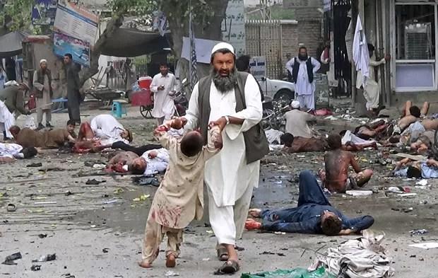 Homem retira criança querida de local de explosão em Jalalabad neste sábado (18) (Foto: Pajwak News Agency/Reuters)