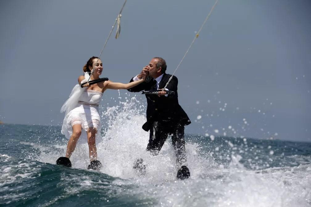 29 de maio - O libanês Tommy beixa a mão de sua noiva Nadine enquanto praticam esqui aquático com os trajes do seu casamento na baía de Jounieh, a norte de Beirute (Foto: Patrick Baz/AFP)
