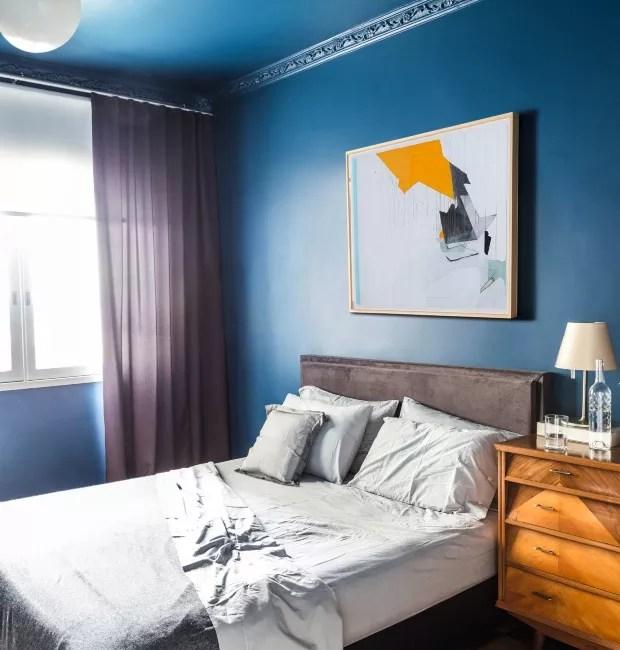 Quarto de casal. Uma cápsula azul que manteve ornamentos do teto originais tem cama com cabeceira de camurça cinza, luminária Melampo, da Artemide, e, na parede, desenho de Guilherme Dable (Foto: Mariana Boro / Editora Globo)