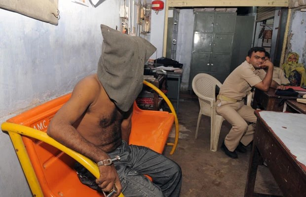 Govindbhai Rathod, de 40 anos, é visto emcapuzado em delegacia em Ahmedabad, na Índia (Foto: Sam Panthaky/AFP)