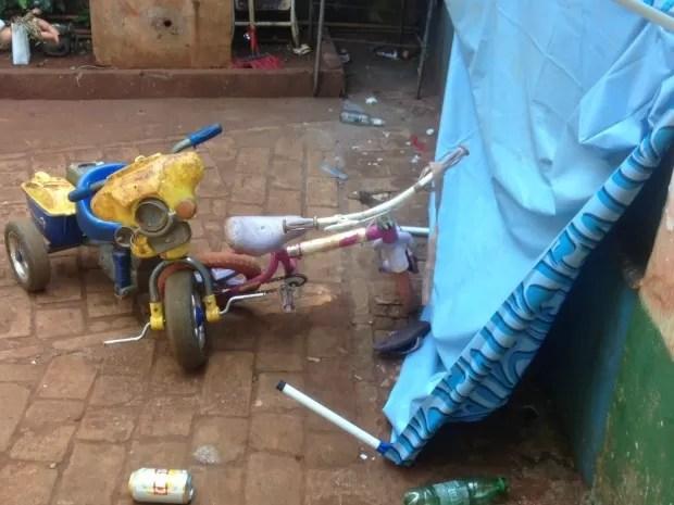 Brinquedos das crianças, lata e garrafa de bebidas alcoólicas no quintal da casa (Foto: Nadyenka Castro/G1 MS)