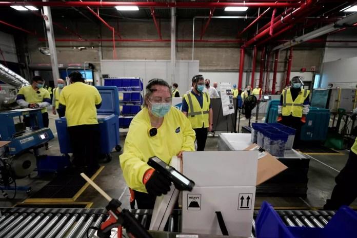 Funcionários de fábrica da Pfizer, em Michigan, embalam as primeiras doses da vacina contra a Covid-19 — Foto: Morry Gash/Pool/Reuters