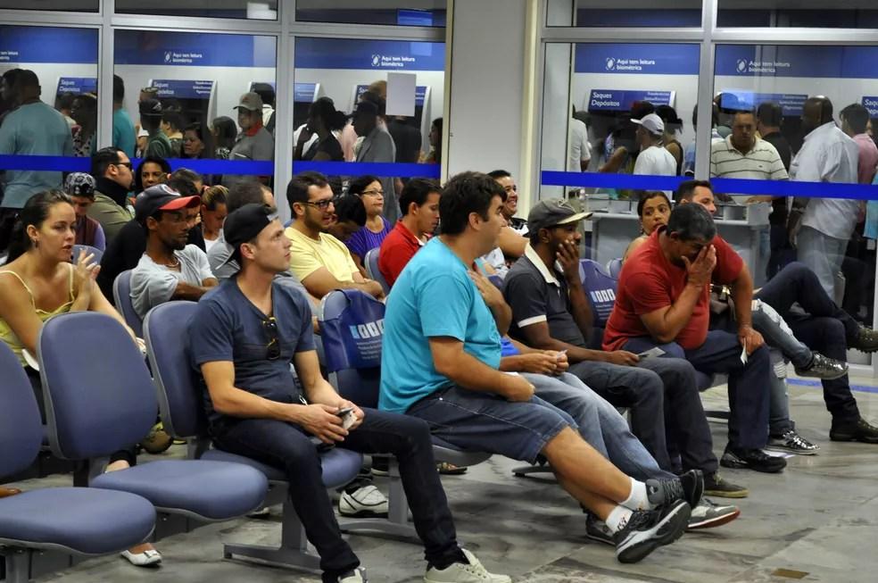 Pessoas aguardar para sacar contas inativas do FGTS na Caixa Econômica Federal (Foto: Lara Silva/G1)