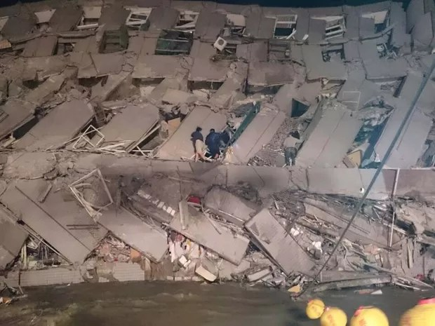 Equipe de resgate entra em escombro de edifício que desabou neste sábado (6) na cidade de Tainan, no Taiwan, por terremoto (Foto: AP Photo)