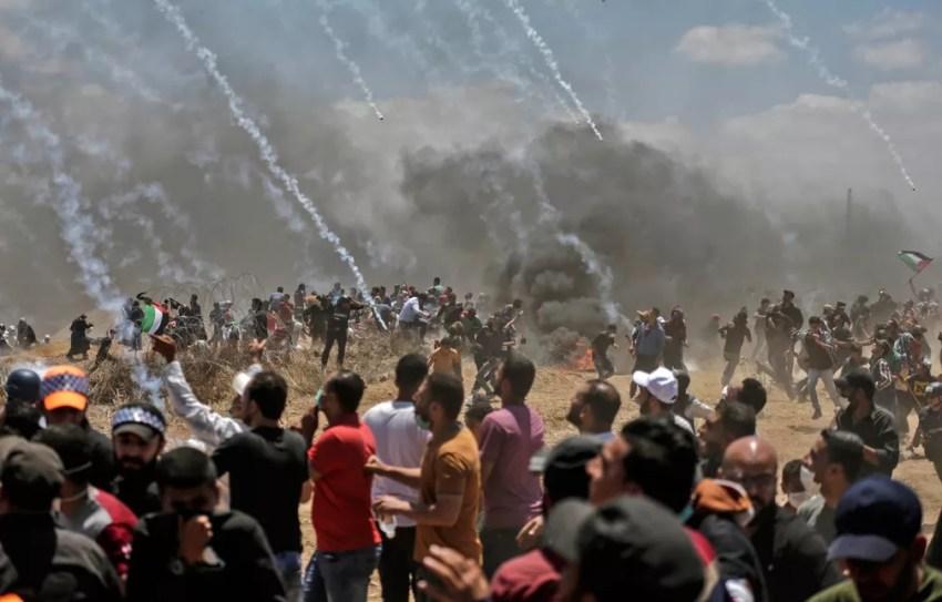 Palestinos correm para se proteger de bombas de gás atiradas por tropas israelenses na fronteira entre Gaza e Israel após protestos contra a inauguração da embaixada dos EUA em Jerusalém (Foto: Mahmud Hams/AFP)