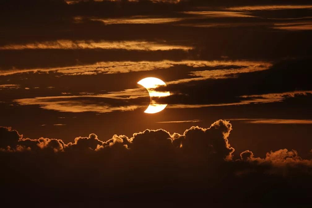 Eclipse solar anular é observado entre nuvens em Arbutus, no estado de Maryland, nos Estados Unidos, no dia 10 de junho — Foto: Julio Cortez/AP