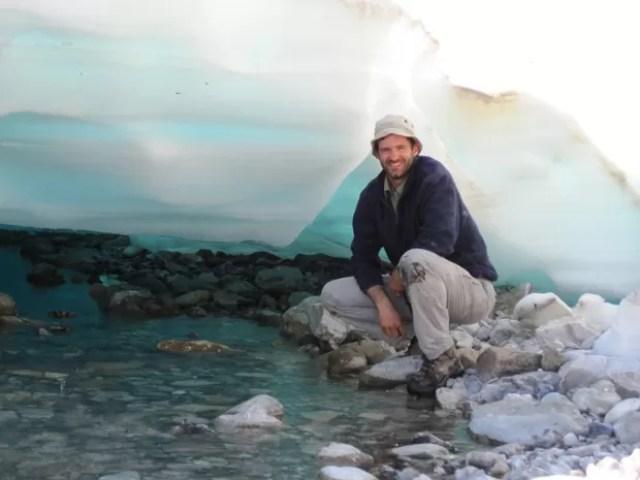 O pesquisador Mark Urban, um dos autores do estudo, posa junto ao gelo em processo de derretimento no Alasca (Foto:  Heidi Golden/Divulgação)