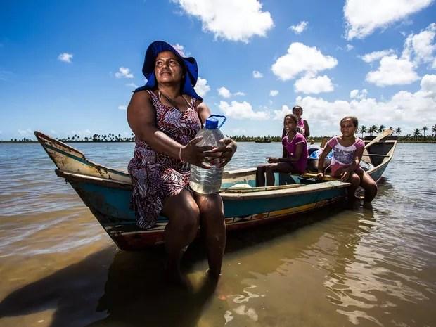 Famílias inteiras navegam rio acima para conseguir água doce (Foto: Jonathan Lins/G1)